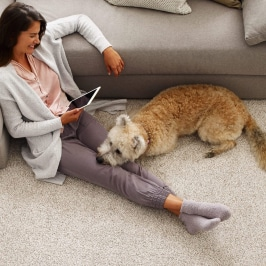 Woman with pet on Carpet | Gillenwater Flooring